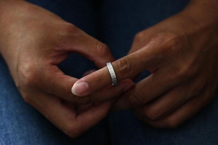 Liu, whose husband Li Zhijin was onboard Malaysia Airlines Flight MH370, tries her husband's ring on her finger in Beijing on July 22, 2014. -- PHOTO: REUTERS