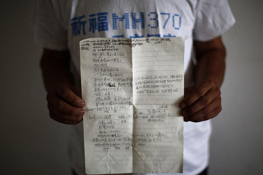 Zhang Yongli, whose daughter Zhang Qi was onboard Malaysia Airlines Flight MH370, shows a note featuring a poem which he wrote for his daughter, in Beijing on July 22, 2014. -- PHOTO: REUTERS