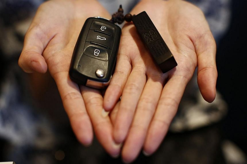 Zhang, whose husband Wang Houbin was onboard Malaysia Airlines Flight MH370, shows her husband's car key and key holder in Beijing on July 18, 2014. -- PHOTO: REUTERS