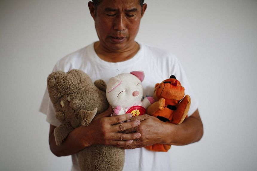 Zhang Yongli, whose daughter Zhang Qi was onboard Malaysian Airlines Flight MH370, looks at his daughter's plush toys in Beijing on July 22, 2014. His wife sometimes roams several kilometres from home because she cannot stand staying in their home, f
