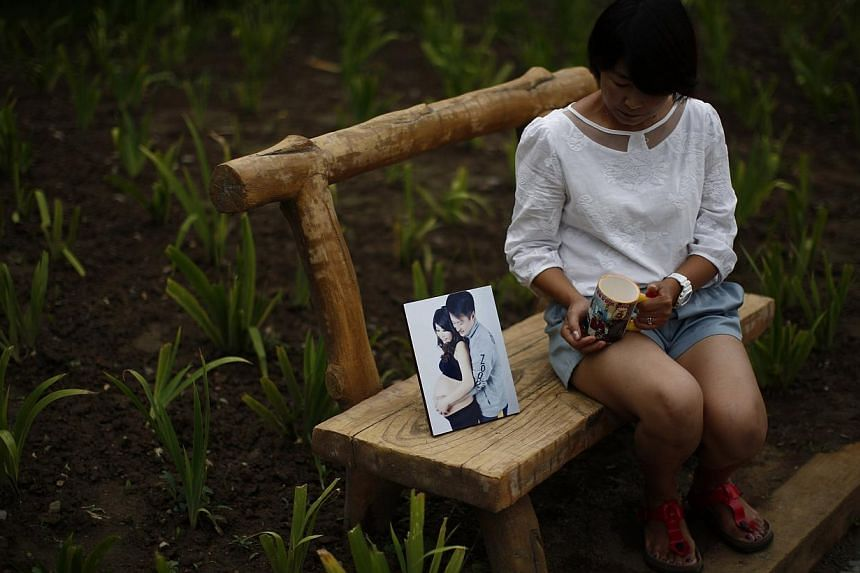 Cheng Liping, whose husband Ju was onboard Malaysia Airlines Flight MH370, shows a picture of her with her husband, at a park near her house which the couple used to visit. Cheng said her life has totally changed since the incident. Their two little