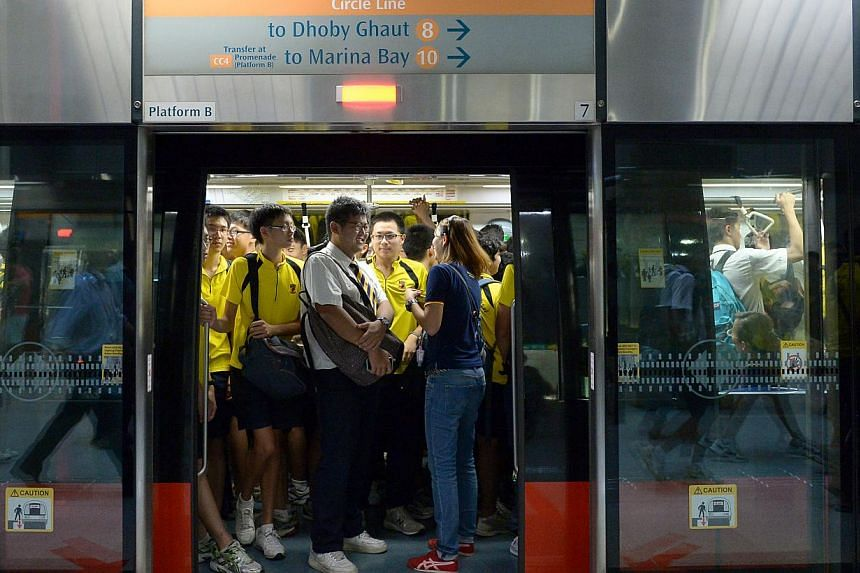 ACS students and teachers cram into one of the five trains that the school have chartered to ferry them from One North station to Stadium station to catch the rugby match. -- PHOTO: ST FILE
