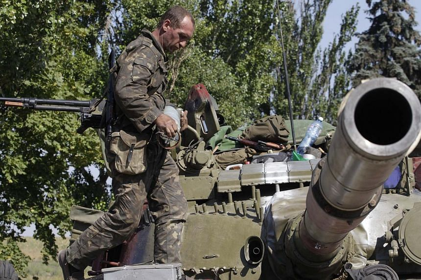 A Ukrainian serviceman loads a shell onto a tank at a checkpoint in the coastal town of Mariupol on Sept 5, 2014. -- PHOTO: REUTERS