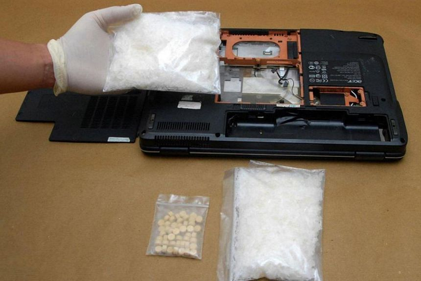 Ice, Ecstasy tablets and a laptop that were seized in a CNB operation on Sep 5,2014.-- PHOTO:CENTRAL NARCOTICS BUREAU