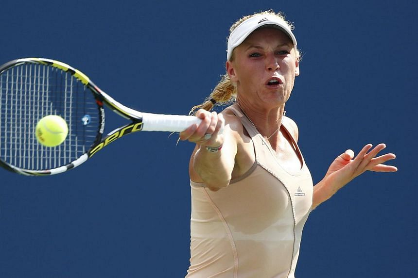 Caroline Wozniacki of Denmark hits a return to Peng Shuai of China during their semi-final match at the 2014 US Open tennis tournament in New York on Sept 5, 2014. -- PHOTO: REUTERS