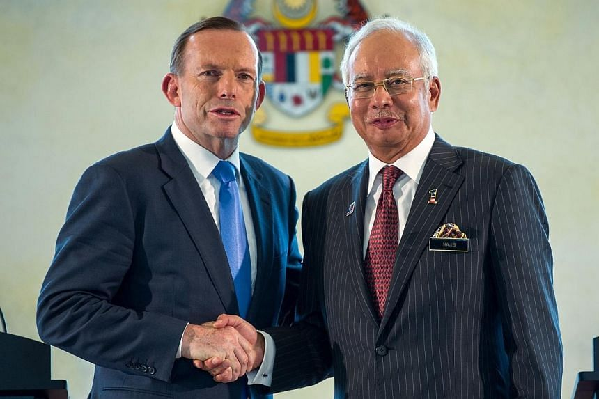Malaysia's Prime Minister Najib Razak (right) shakes hands with his Australian counterpart Tony Abbott after a joint press conference at the prime minister's office in Putrajaya, outside Kuala Lumpur on Saturday, Sept 6, 2014.The search for Mal