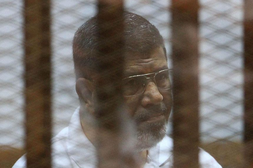 Egypt's deposed Islamist president Mohamed Mursi, charged along with 130 others of plotting attacks and escaping from prison in 2011, sits inside the defendant's cage during his trial at the police academy in Cairo on Aug 18, 2014.An Egyptian