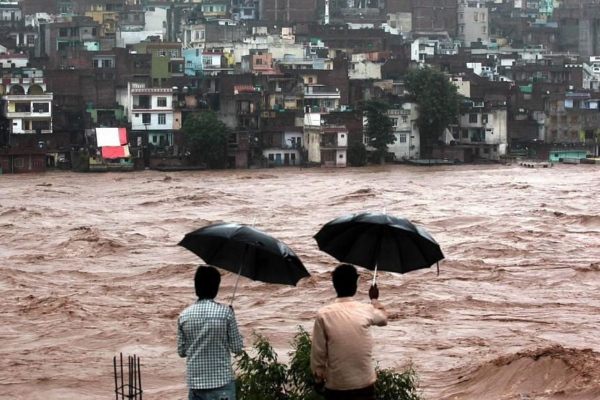 Indian residents look on towards threatened houses as waters from the overflowing Tawi river rage past in Jammu on Sept 6, 2014. -- PHOTO: AFP