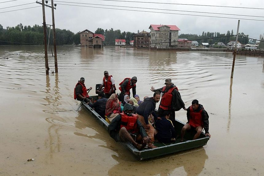 Indian army soldiers paddle a raft as they assist Kashmiri residents during flood rescue operations on the outskirts of Srinagar on Sept 6, 2014. -- PHOTO: AFP