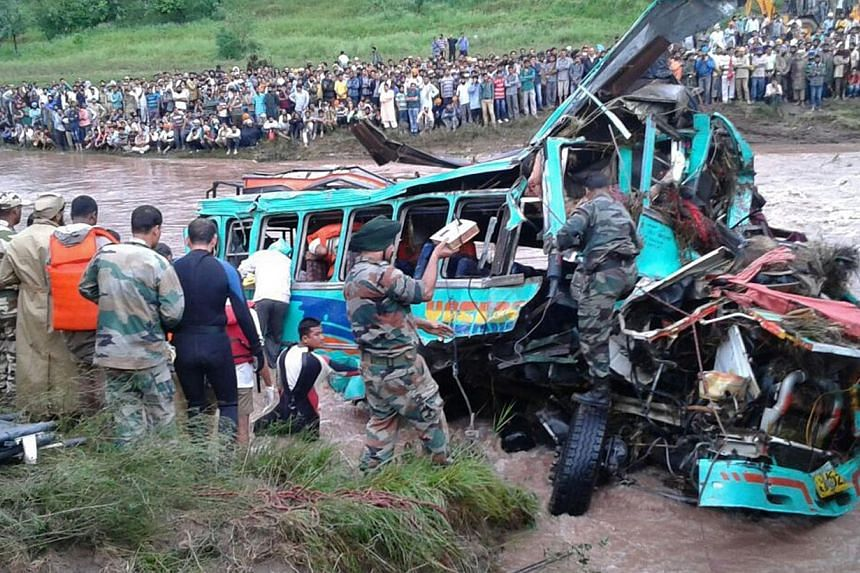Rescue workers recovering the wreckage of a bus that was swept away by flash floods in the Nowshera area of Rajouri district, some 120kms from Jammu on Sept 4, 2014. -- PHOTO: AFP
