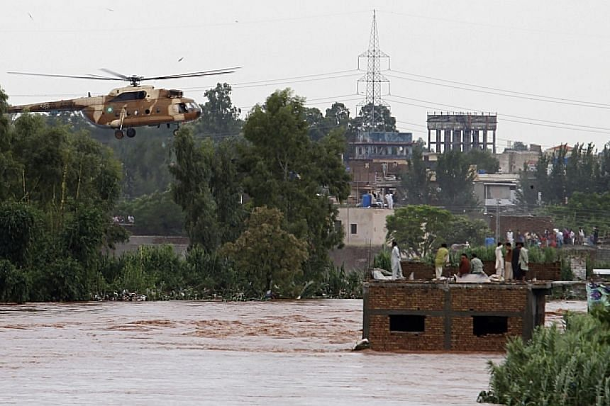 A Pakistani Army Mi-17 helicopter hovers as it prepares to rescue trapped residents during a flood evacuation operation on the outskirts of Islamabad on Sept 5, 2014. -- PHOTO: AFP