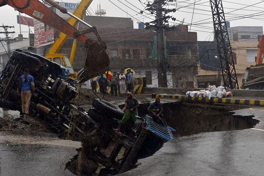 Pakistani workers pull out a truck from a sinkhole on a road during heavy monsoon rain in Lahore on Sept 5, 2014. -- PHOTO: AFP