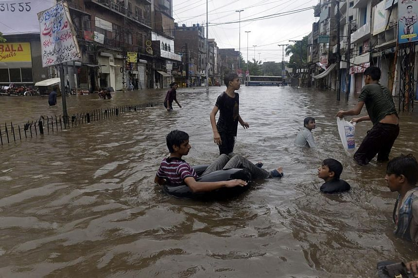 Pakistani youths play in a flooded street during monsoon rain in Lahore on Sept 5, 2014. -- PHOTO: AFP