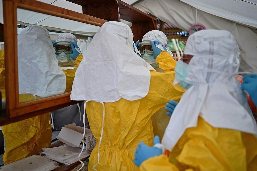 """MSF medical workers put on protective clothing at an MSF Ebola treatment facility in Kailahun, on Aug 15, 2014.Sierra Leone is to enforce three days of """"complete shutdown"""" across the country later this month in a bid to contain the Ebola epidem"""