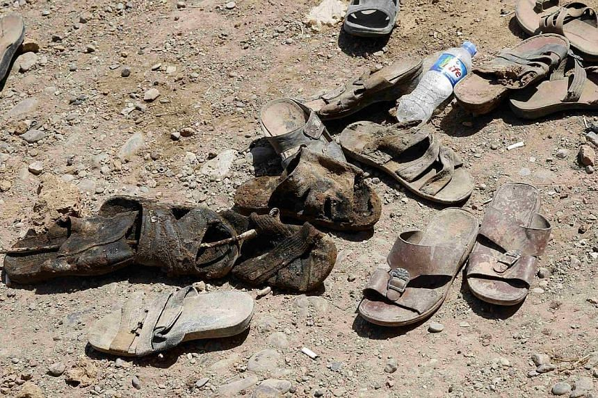 The shoes of men who were recently dug up from a mass grave are seen outside the town of Sulaiman Pek in northern Iraq on Sept 5, 2014. -- PHOTO: REUTERS