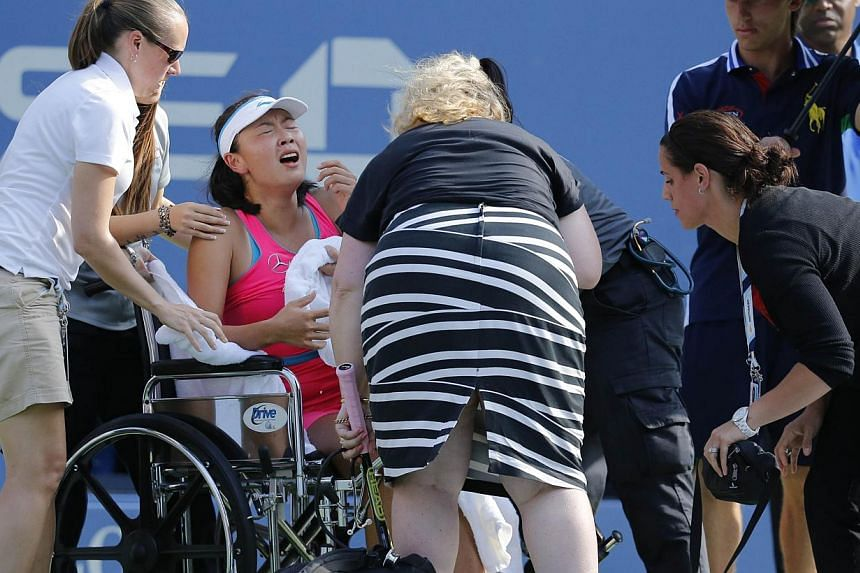 Peng Shuai of China receives help leaving the court in her match against Caroline Wozniacki of Denmark during their US Open 2014 women's singles semifinals match at the USTA Billie Jean King National Center in New York onSept 5, 2014. -- PHOTO: