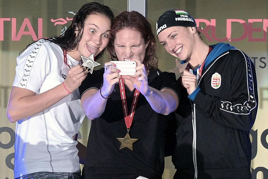 Melanie Schlanger (centre) of Australia takes a selfie with Katika Hosszu (right) of Hungary and Jeanette Ottesen of Denmark (left) on the podium for the women's 100 LC metre freestyle during the Prudential Singapore Swim Stars on Sept 5, 2014. The P