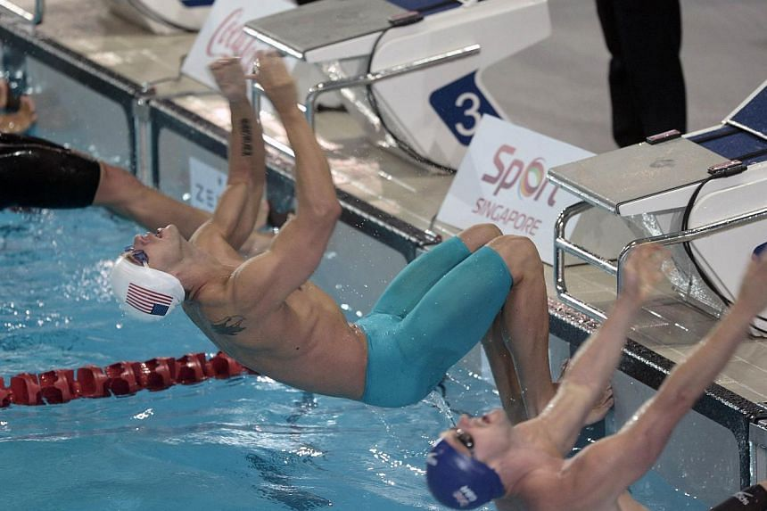 David Plummer (centre) of the US and Liam Tancock of Britain dive in the men's 100 LC metre backstroke during the Prudential Singapore Swim Stars on Sept 5, 2014. The Prudential Singapore Swim Stars inaugural one-day swimming event saw the participat