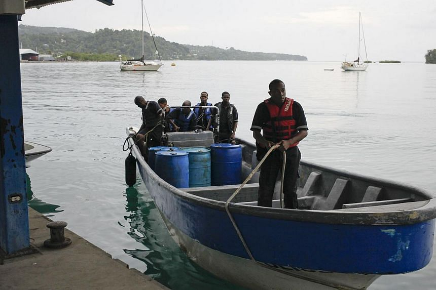 Members of Jamaica's Marine Police return to port after leaving the site where it is presumed a small US private plane with an unresponsive pilot crashed off the east coast of Jamaica, in Port Antonio on Sept 5, 2014. -- PHOTO: REUTERS