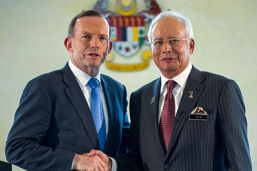 Malaysia's Prime Minister Najib Razak (right) shakes hands with his Australian counterpart Tony Abbott after a joint press conference at the prime minister's office in Putrajaya, outside Kuala Lumpur on Sept 6, 2014. -- PHOTO: AFP