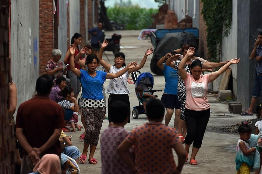 A group of women take part in an early morning dance session, as villagers look on, in Weijian village, in China's Henan province on July 30, 2014.Some have labelled the dancing women ridiculous and annoying, while others believe that they dese