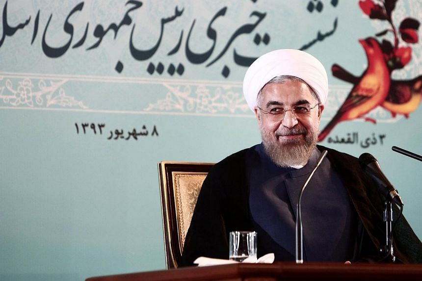 Iranian President Hassan Rouhani smiles during a press conference in Tehran on Aug 30, 2014. -- PHOTO: AFP