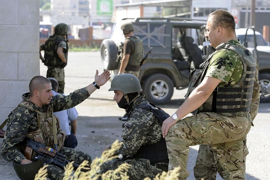 Ukrainian servicemen stand guard on Sept 7, 2014 at a Ukrainian army checkpoint on the outskirts of the key southeastern port city of Mariupol, after an overnight bombing attack. -- PHOTO: AFP