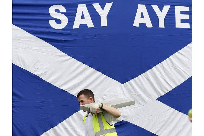 A workman walks past a Scottish saltire in Kilmarnock, Scotland on Sept 3, 2014.The British government is scrambling to respond to a lurch in the opinion polls towards a vote for Scottish independence this month by promising a range of new powe