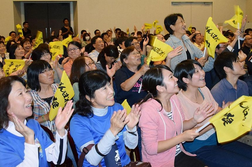 Supporters of Japanese tennis player Kei Nishikori cheer while watching the US Open tennis semi-final match at Nishikori's home town of Matsue city on Sept 7, 2014. -- PHOTO: AFP