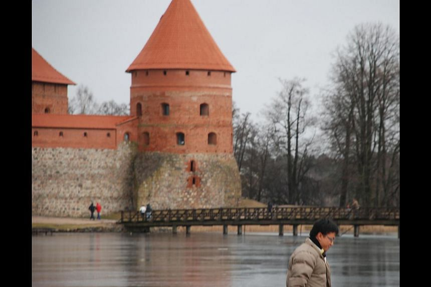 Mr Jianggan Li (above) at Trakai (left), a historic city and lake resort which lies west of Lithuania's capital Vilnius.