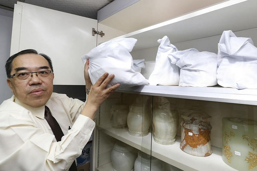 Trinity Casket operations manager Dave Lim with the uncollected bags of ashes, kept in a cabinet in his office in Sin Ming Drive. The oldest bag dates back to 1997. -- ST PHOTO: CHEW SENG KIM