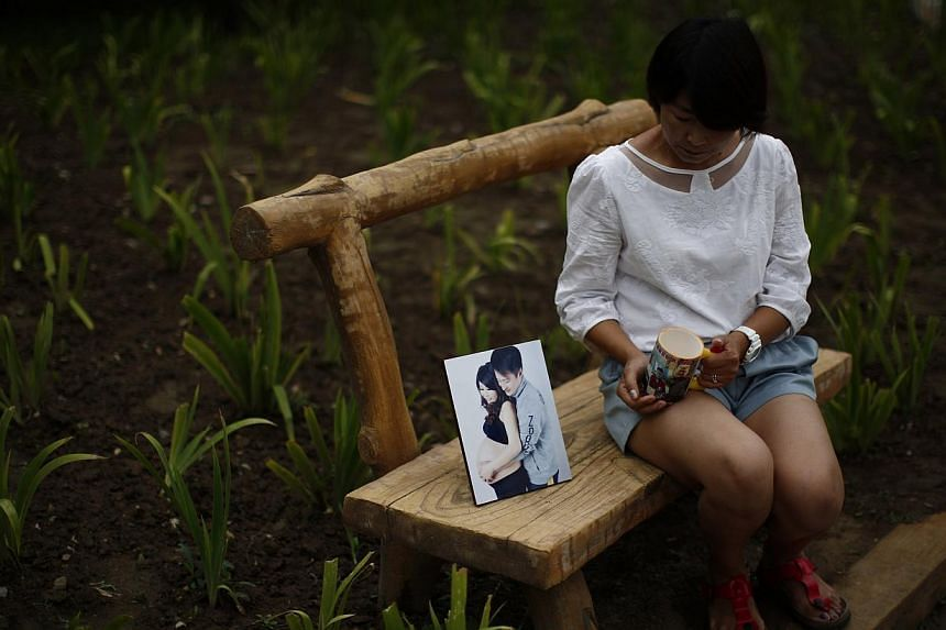 Ms Cheng Liping, whose husband Ju was onboard Malaysia Airlines Flight MH370 which disappeared on March 8, 2014 shows a picture which features she and her husband together, and her husband's cup, at a park near her house where she and her husband use