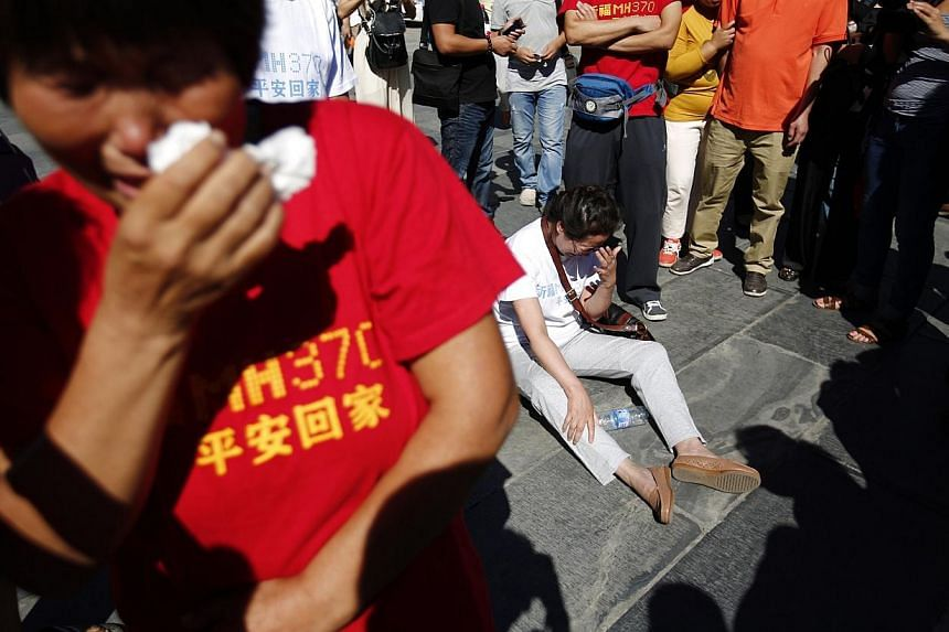 Family members of passengers onboard the missing Malaysia Airlines Flight MH370, cry as they gather to pray at Yonghegong Lama Temple in Beijing on Sept 8, 2014, on the six-month anniversary of the disappearance of the plane. -- PHOTO: REUTERS