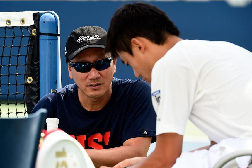 Kei Nishikori (right) of Japan talks with coach Michael Chang (left) during a practice session on Day 14 of the 2014 US Open at the USTA Billie Jean King National Tennis Center on Sept 7, 2014, in Flushing in New York City. -- PHOTO: AFP