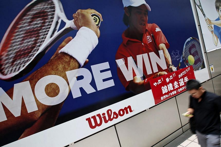 A man holding his mobile phone walks in front of a poster of tennis player Kei Nishikori of Japan outside a sports shop in Tokyo on September 8, 2014. -- PHOTO: REUTERS