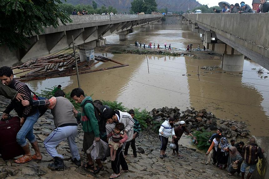 Kashmiri residents walk along an embankment on the side of a bridge as they head for a higher ground during flooding on the outskirts of Srinagar on Sept 6, 2014. Desperate residents were huddled on rooftops on Monday, Sept 8, as they tried to s