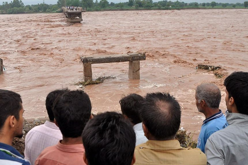 Indian villagers look on at a missing section of a bridge across the overflowing Tawi river that was swept away as flooding continues in the Mandal area of Jammu on Sept 6, 2014. The prime ministers of India and Pakistan have offered to help eac