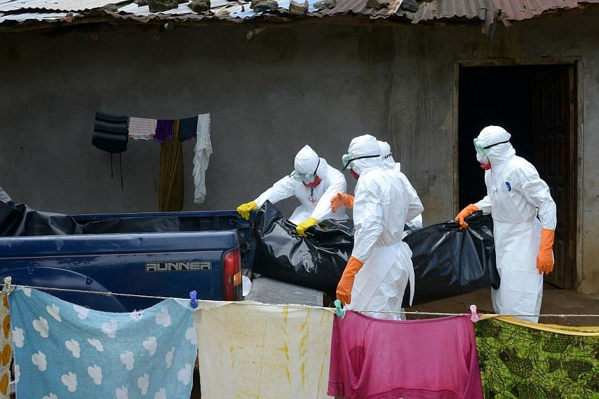 Liberian Red Cross health workers wearing protective suits carry the body of a victim of the Ebola virus in Banjor on the outskirts of Monrovia on Sept 4, 2014. -- PHOTO: AFP