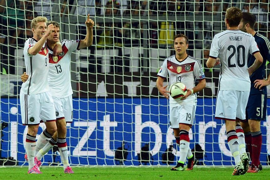 Germany's midfielder Thomas Mueller (second, left) celebrates with his teammates Germany's midfielder Andre Schuerrle (left), Germany's forward Mario Goetze (centre, with the ball) and Germany's midfielder Christoph Kramer (second, right) after scori