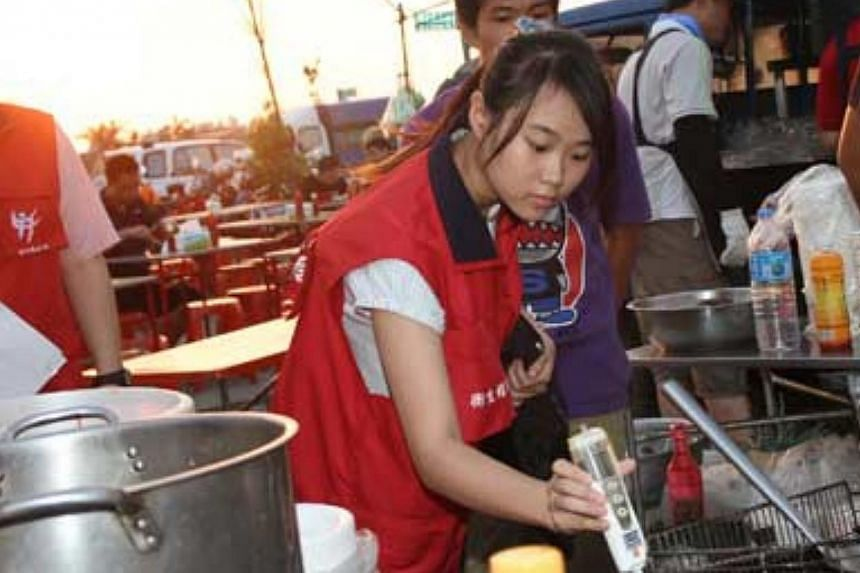 A staff member from the Public Health Bureau of Hsinchu County government in Taiwan uses inspection equipment to check oil used in a night market. Hong Kong is conducting food tests now as fears mount that Taiwan's gutter oil scandal could have sprea