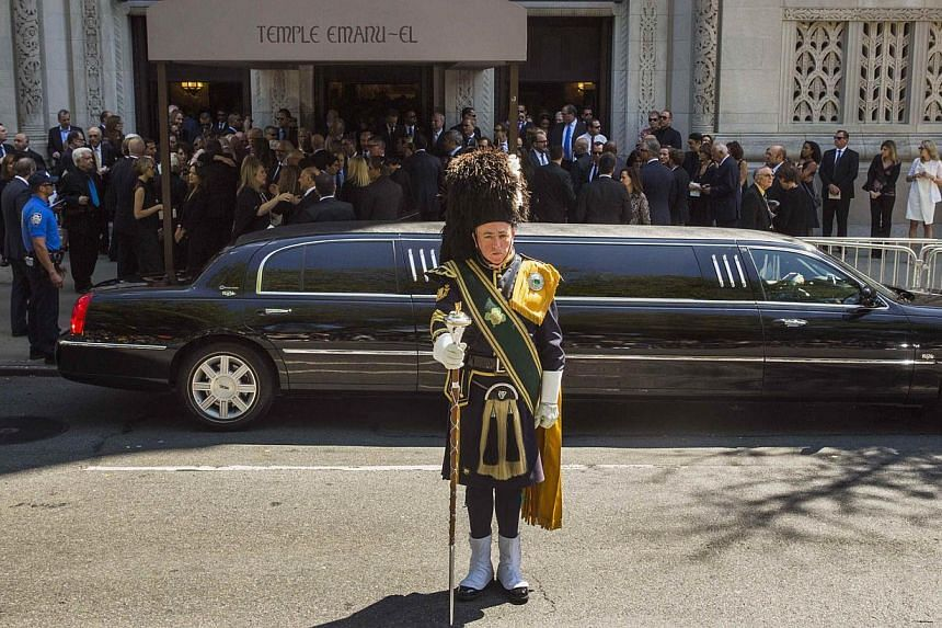 A member of a bagpipe ensemble looks on as mourners depart the funeral of comedian Joan Rivers at Temple Emanu-El in New York on Sept 7, 2014. -- PHOTO: REUTERS