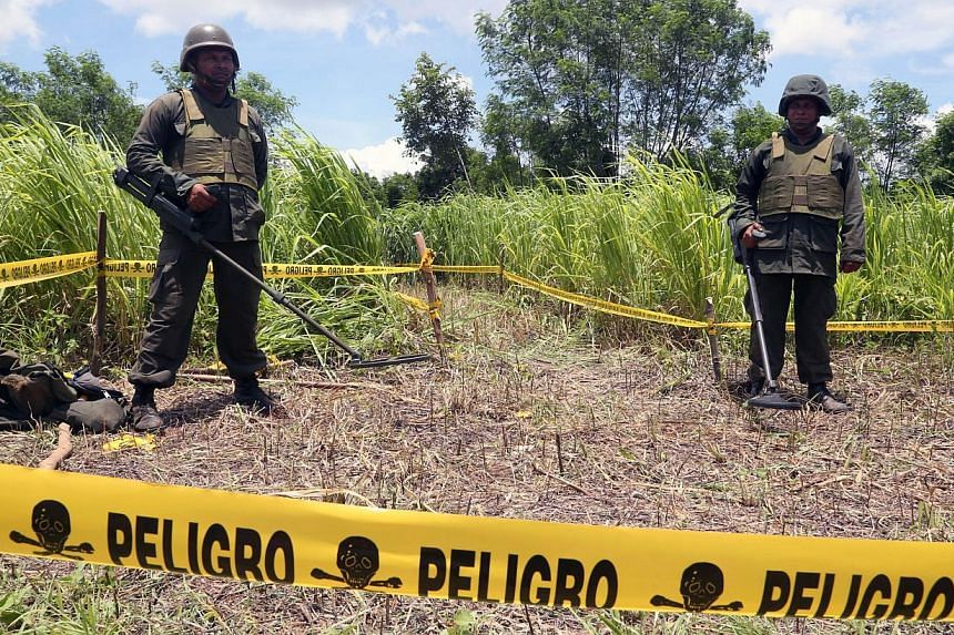 Handout picture released by the Nicaraguan presidency press office showing two Nicaraguan soldiers standing guard in the site where an alleged meteorite struck in Managua on Sept 7, 2014. -- PHOTO: AFP
