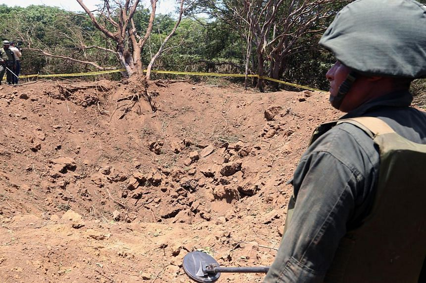 Handout picture released by the Nicaraguan presidency press office showing a Nicaraguan soldier checking the site where an alleged meteorite struck in Managua on Sept 7, 2014. -- PHOTO: AFP