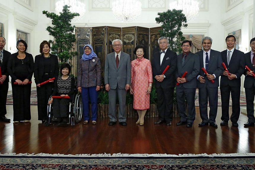 President Tony Tan Keng Yam (in grey suit) and his wife Mary (in red), and Speaker of Parliament Halimah Yacob (fifth from left) at the appointment ceremony of the Nominated Members of Parliament at the Istana on Aug 26, 2014. -- PHOTO: ST FILE