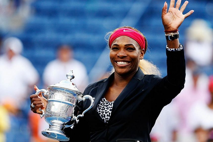 Serena Williams of the United States celebrates with the trophy after defeating Caroline Wozniacki of Denmark to win their women's singles final match on Day fourteen of the 2014 US Open at the USTA Billie Jean King National Tennis Center in the Flus