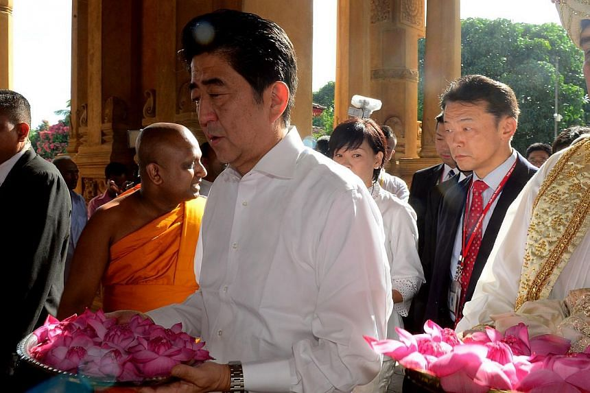 Japanese Prime Minister Shinzo Abe (middle) offered flowers during a visit tp the historic Kelaniya Rajamaha temple in Colombo on Sept 8, 2014, which Buddhists believe was visited by Buddha himself more than 2,500 years ago. -- PHOTO: AFP