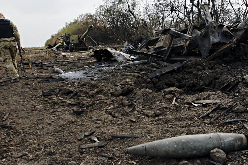 A Ukrainian serviceman walks past a column of destroyed military equipment near the village of Talakovka, some 22 kms northeast of Mariupol, after an overnight bombing attack, on Sept 7, 2014. -- PHOTO: AFP