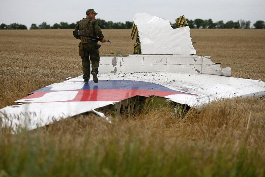 An armed pro-Russian separatist stands on part of the wreckage of the Malaysia Airlines Boeing 777 plane after it crashed near the settlement of Grabovo in the Donetsk region on July 17, 2014. -- PHOTO: REUTERS