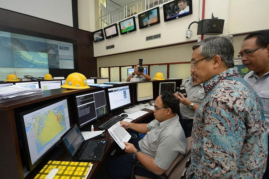 Andi Eka Sakya (2nd right), head of Indonesia's Agency for Meteorological, Climatological and Geophysics (BMKG), and Mochammad Riyadi (back right), director for the Earthquake and Tsunami Center in Jakarta, examine the Indian Ocean-wide tsunami exerc