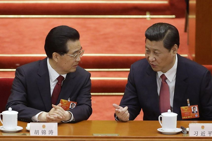 China's newly-elected President Xi Jinping (right) talks with China's former President Hu Jintao during the fourth plenary meeting of the National People's Congress (NPC) at the Great Hall of the People in Beijing on March 14, 2013.-- PHOTO: RE
